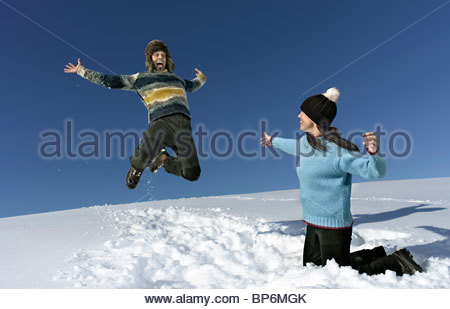 Mid adult couple playing in snow, man jumping in air - Stockfoto