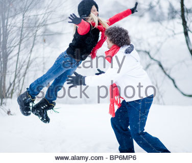 Young man catching young woman leaping in midair on winter day - Stockfoto