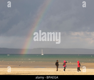 People on beach with a rainbow in the distance in Weymouth, Dorset, UK. - Stock Photo
