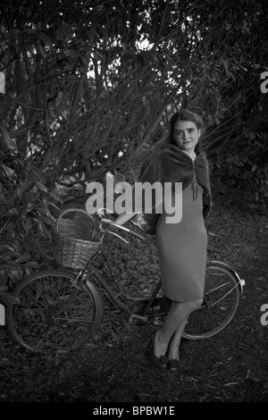 Girl with a bicycle in a vintage 1940 style - Stock Photo