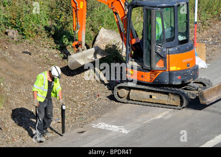 Road works on M25 motorway hard shoulder workman using  Scope pipe and cable locator - Stock Photo