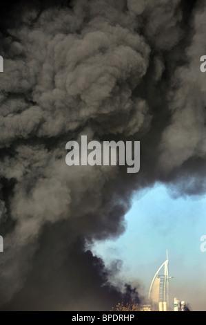 A dark cloud of smoke in front of the Burj al Arab Hotel, Dubai, United Arab Emirates - Stock Photo