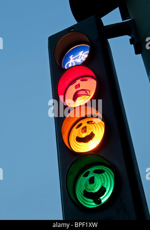 faces drawn onto cycle traffic lights at dusk in Berlin Germany - Stock Photo