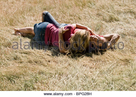 A young couple lying on the grass, embracing - Stock Photo