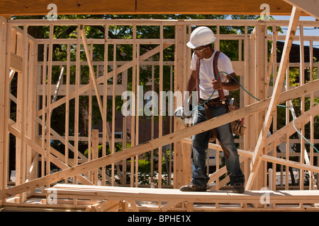 Carpenter standing at a construction site holding a nail gun - Stockfoto