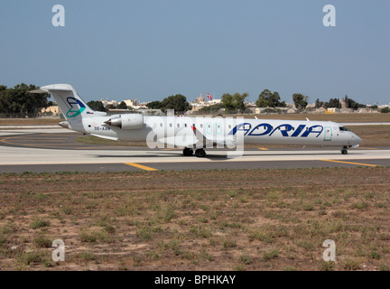 Commercial aviation. Adria Airways Bombardier CRJ900 regional airliner on arrival in Malta - Stock Photo