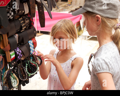Two girls six and ten year old looking at bracelets on the market in Pisa, Tuscany, Italy - Stock Photo