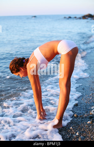 Beautiful brunette doing physical exercises on the beach. - Stock Photo