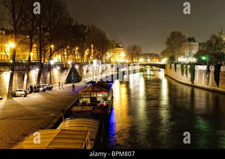 Night view of the Seine near Notre Dame de Paris as viewed from Pont de l'Archeveche - Stock Photo