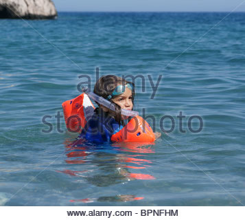 Little boy playing alone learning to swim wearing orange inflatable armbands water wings - Stock Photo