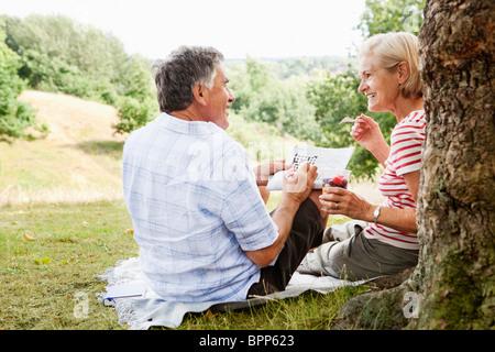 Couple doing crossword, sitting in park - Stock Photo