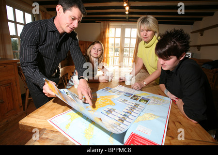 Image shows a family looking at a map of New Zealand where they plan to emigrate to and start a new life. Photo:Jeff - Stock Photo