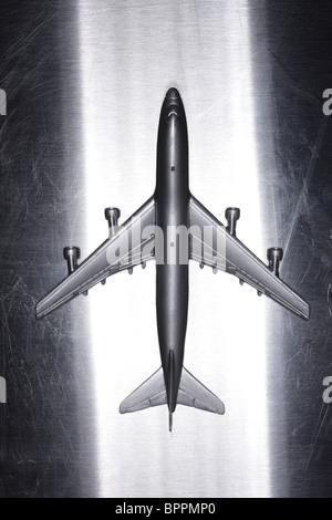 Metal toy airplane on metallic surface - Stock Photo