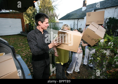Image shows a happy family moving house, loading cardboard boxes together into their car. Photo:Jeff Gilbert - Stock Photo