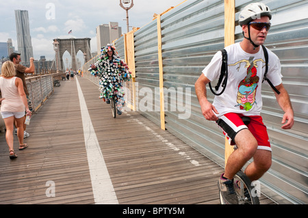 Gene Pool, aka The Can Man, crossing the Brooklyn Bridge on his unicycle as part of the Brooklyn Long Distance Unicycle - Stock Photo