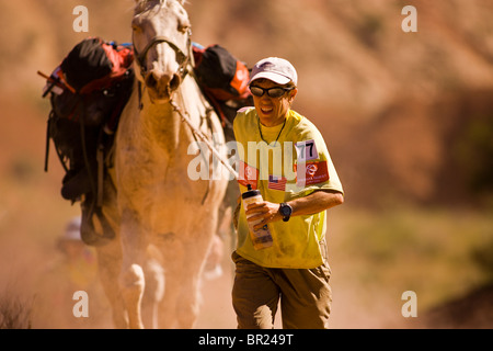 Adventure racer running and leading a horser in a race in Moab, Utah. - Stock Photo