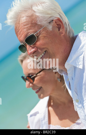 Happy senior man and woman couple together looking out to sea on a deserted tropical beach with bright clear blue - Stock Photo