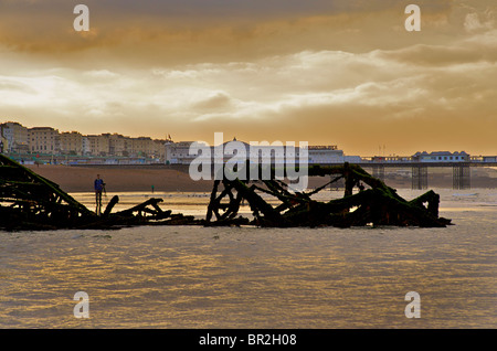 Silhouetted remnants of the West Pier with The Palace Pier beyond Brighton. East Sussex, England - Stock Photo