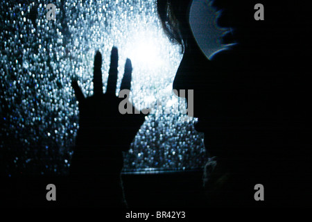 A lady holds hand to a window with rain drops on it, San Diego, California. - Stock Photo