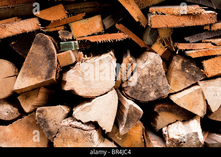 Stacked chopped fire wood outside a house in Kent England - Stock Photo