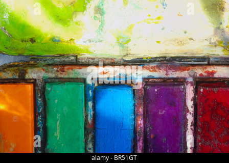 Artist's vintage used watercolor paintbox, big close up on orange, green, blue, purple and red paint blocks and - Stock Photo