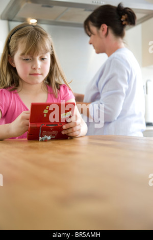 Girl Playing with Handheld Video Game in the Kitchen - Stock Photo