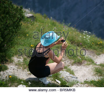 Taking pictures with a digital COMPACT BRIDGE digital camera - woman in nature with camera - Stock Photo