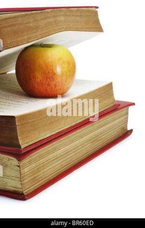 Red apple in between pages of old book on white background - Stock Photo