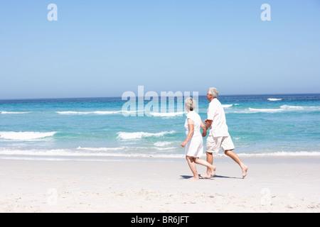 Senior Couple On Holiday Running Along Sandy Beach - Stock Photo