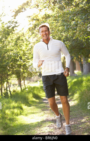 Middle Aged Man Jogging In Park - Stock Photo