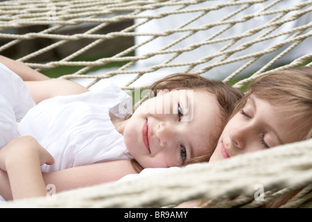 sisters resting in a hammock - Stock Photo