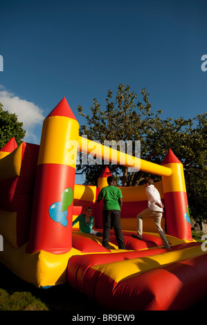 Children playing on an inflated bouncy castle, UK - Stock Photo