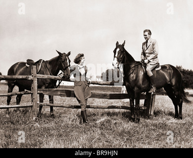 1930s 1940s COUPLE IN RIDING GEAR MAN RIDING HORSE WOMAN STANDING BY WOODEN FENCE - Stock Photo