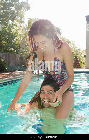 Young woman on young man's shoulders in swimming pool - Stock Photo