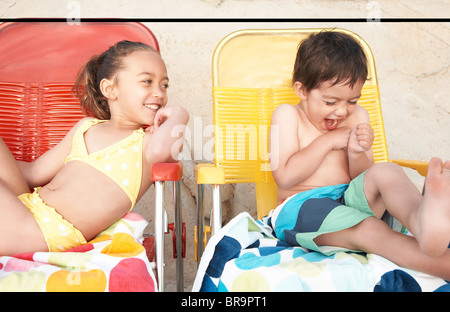 Kids in bathing suits on lounge chairs - Stock Photo