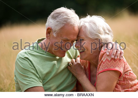 A senior couple sitting on the grass, laughing - Stock Photo