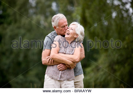 A senior couple standing in a field, laughing - Stock Photo