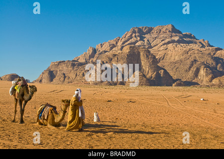 Bedouin with his camels in the stunning scenery of Wadi Rum, Jordan, Middle East - Stock Photo