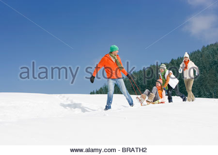 Father pulling wife on sled through snow as children push - Stock Photo