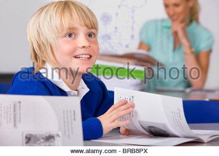 Bored school boy reading workbook in classroom - Stock Photo