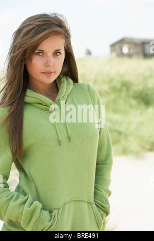 Young Woman Standing On Beach Wearing Hooded Top With Old Beach Hut In Distance - Stock Photo