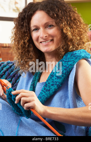 Close Up Of Woman Sitting In Chair Knitting - Stock Photo