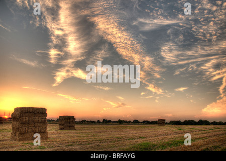 Haystack in a field at sunset. Landscape cloud vista wide angle low view warm evening haystacks orb red blue gold - Stock Photo