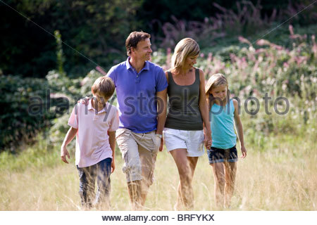 A family walking through a field, close-up - Stock Photo
