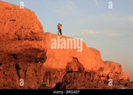 Man and a woman on top of the rock in Praia de Gale, Algarve, Portugal - Stock Photo