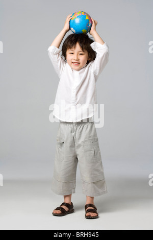 Little boy holding a globe - Stock Photo