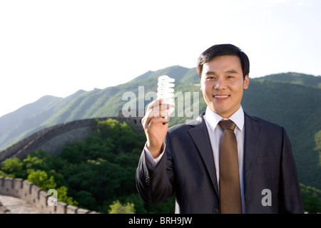 Businessman holding a light bulb while on the Great Wall - Stock Photo