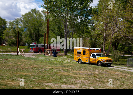 A rural fire departments paramedics treating a man injured by a falling tree - Stock Photo