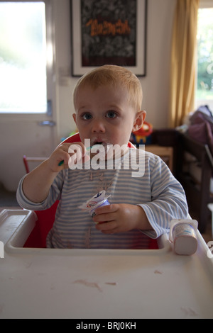 Young boy 16 months old eating a messily eating yogurt. Hampshire, England. - Stock Photo