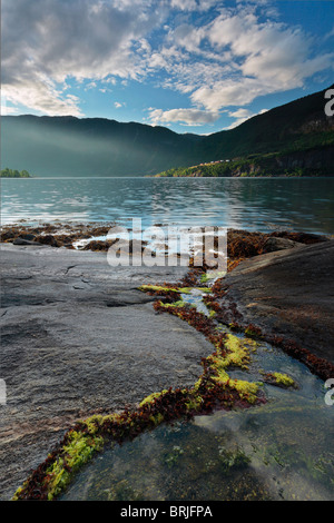 Sun beams break through the clouds and illuminate the opposite shore of Sognefjord in Norway - Stock Photo